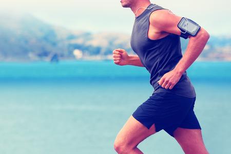 deporte: Cardio running escuchando m�sica smartphone. Trotar cuerpo irreconocible en la playa de mar o frente al mar que se resuelve con la frecuencia cardiaca dispositivo de aplicaci�n de monitor y auriculares en verano.