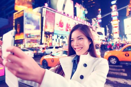 幸せな女観光タブレット ニューヨーク市、マンハッタン、タイムズスクエアで写真画像の selfie を取るします。アジア コーカサス地方民族に喜びと 写真素材