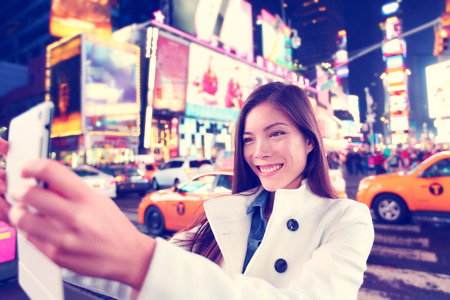 Happy woman tourist taking photo picture selfie with tablet in New York City, Manhattan, Times Square. Multiethnic Asian Caucasian woman in her 20s joyful and happy smiling wearing spring pea coat.