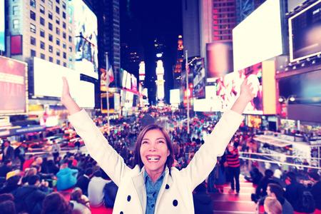 Succes en leuk- Gelukkig opgewonden vrouw in New York, Manhattan, Times Square toejuichen vieren blij met opgeheven armen. Vrolijke multi-etnische Aziatische Kaukasische jonge stedelijke professionele in haar jaren '20.