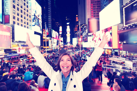 spring time: Success and fun- Happy excited woman in New York City, Manhattan, Times Square cheering celebrating joyful with arms raised. Cheerful Multiethnic Asian Caucasian young urban professional in her 20s.