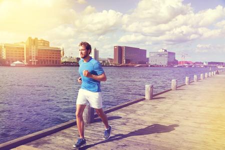 adult: Urban man runner running in Copenhagen city, Denmark. Danish male adult jogging in Bryggen, Copenhagen, Scandinavian Europe.