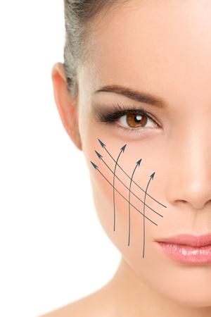Lifting facial tratamiento anti-envejecimiento - Retrato de mujer asiática con líneas gráficas que muestran efecto lifting facial en la piel perfecta. Skincare concepto cosmético.