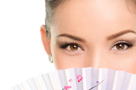 아시아 아름다움의 눈 - 메이크업 여자가 동양 팬을 찾고. 액세서리 뒤에 아이 라이너와 마스카라 숨어 얼굴을 보여주는 신비한 중국어 아가씨. 스톡 콘텐츠