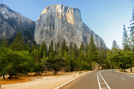 upper half: El Capitan mountain formation and road through Yosemite National Park USA. Road trip in mountain landscape in California showing forest and mountains at sunset in summer.