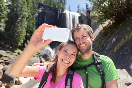 ハイカーのヨセミテ国立公園でハイキングに滝、バーナル滝によってスマート フォンでセルフ ポートレート撮影のアクティブなライフ スタイルの