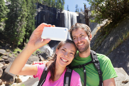 Active lifestyle couple of hikers hiking at Yosemite National Park taking a self-portrait picture with smartphone by waterfall, Vernal Fall. Young hiking couple relaxing in summer nature landscape. Stock Photo
