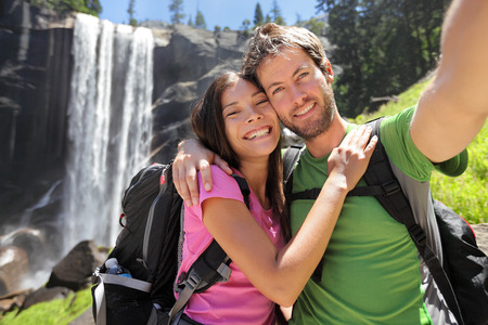 waterfalls: Selfie couple hikers at Yosemite National Park taking a self portrait picture with beautiful waterfall, Vernal Fall. Young hiking couple relaxing after hike in beautiful summer nature landscape.