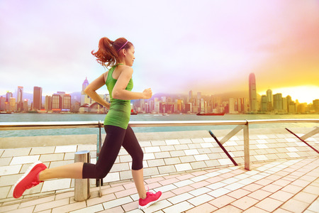 lifestyle: City Running - woman runner and Hong Kong skyline. Asian chinese fitness athlete jogging training living healthy lifestyle on Tsim Sha Tsui Promenade and Avenue of Stars in Victoria Harbour, Kowloon. Stock Photo