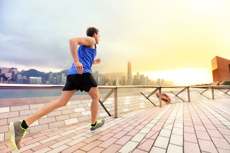 Urban running man runner in Hong Kong city skyline. Caucasian man working out jogging on the promenade of Victoria Harbor in HongKong, China, in afternoon sunset during spring. Stock Photo