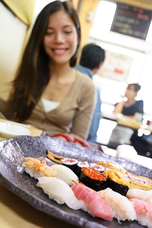 city fish market: Sushi eating woman tourist in Tokyo restaurant. Travel destination famous Tsukiji Fish Market, person looking at plate of raw seafood presented as sashimi. Japanese food. Stock Photo