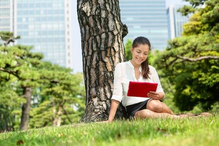 Femme japonaise la lecture en utilisant l'application de la tablette à Tokyo. L'élève adulte jeune étudiant livre électronique avec l'ordinateur pc touchpad eReader ou tablette numérique dans le parc à proximité du quartier de Ginza, le centre-ville de Tokyo, Japon. Banque d'images