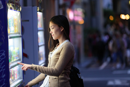 culture: Japan vending machines - Tokyo woman buying drinks. Japanese student or female tourist choosing a snack or drink at vending machine at night in famous Harajuku district in Shibuya, Tokyo, Japan.