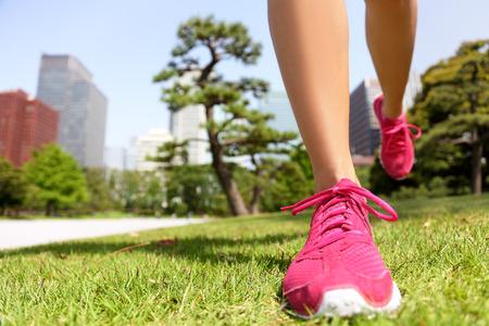 Hardloopschoenen - vrouw runner joggen fit te blijven in Tokio Park, Japan. Close-up van roze trainers in groen gras in de zomer park. Stockfoto