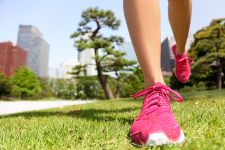 Running shoes - woman runner jogging staying fit in Tokyo Park, Japan. Closeup of pink trainers in green grass in summer park.