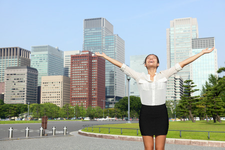 tokyo prefecture: Happy free businesswoman cheering open arms in achievement and success, Japanese woman carefree in front of Tokyo downtown skyline from the outer imperial palace gardens. Stock Photo