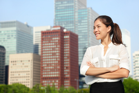 Asian japanese business woman portrait in Tokyo. Happy confident young smart professional in casual business outfit downtown Tokyo with skyline in the background. photo