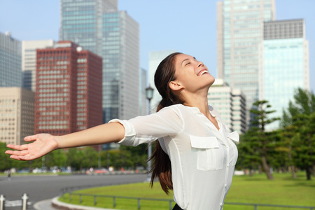 Freedom success businesswoman - Happy free japanese business woman in Tokyo city skyline. Carefree Asian businesswoman arms open up in the sky, Japan. photo
