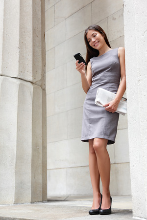 Business woman lawyer using apps on smartphone outside to read news or text sms. Successful young multiracial Caucasian  Asian Chinese professional woman standing in suit dress holding newspapers. photo