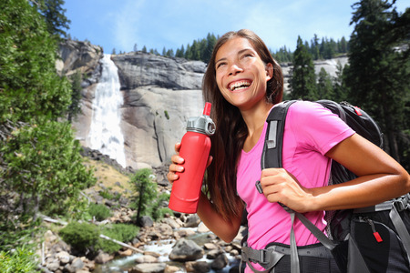 Gezonde wandelaar meisje drinkwater in de natuur wandelen. Mooie jonge vrouw wandelen blij met fles water in de voorkant van de Vernal Fall, Yosemite National Park, California, USA.