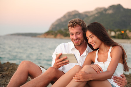 e reading: Romantic couple relaxing on beach using tablet computer at sunset. Young multiracial couple using apps on digital tablet taking pictures or reading e book looking at touch screen together.
