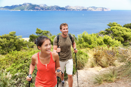 trekking pole: Hikers hiking in Mallorca, mediterranean Europe. Young adults couple walking in beautiful nature landscape on the coast of Mallorca, Balearic Islands, Spain. Famous European summer destination.