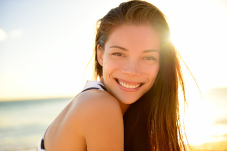 sun: Asian beautiful girl smiling happy on beach vacation enjoying warm sunshine. Mixed race Asian Caucasian pretty model outside with sun in background on Hawaiian tropical beach. Stock Photo