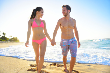 Young interracial romantic beautiful couple walking in beach sand holding hands smiling happily. Relaxed mixed race couple enjoying romance on vacation travel. Asian woman, Caucasian man. Stok Fotoğraf - 36753478