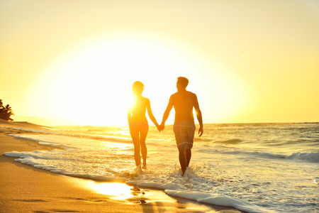 sunbeam: Honeymoon romantic couple in love holding hands walking on beautiful sunset at beach in waterfront. Lovers or newlywed married young couple by the sea enjoying relaxed vacation travel holiday. Hawaii. Stock Photo