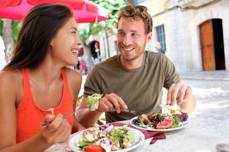 gezonde mensen: Restaurant toeristen paar eten op terrasje. Reizen zomer mensen het eten van gezond voedsel bij elkaar tijdens de lunch tijdens een vakantie in Mallorca, Spanje. Aziatische Kaukasische multiraciale jonge volwassenen. Stockfoto