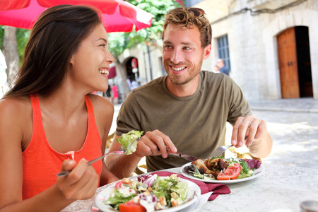 Restaurant tourists couple eating at outdoor cafe. Summer travel people eating healthy food together at lunch during holidays in Mallorca, Spain. Asian Caucasian multiracial young adults. Stok Fotoğraf