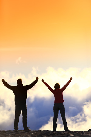 Success, life achievement, goal accomplishment concept with hiking people cheering and celebrating of joy with arms raised outstretched up in the sky outside on mountain summit. photo