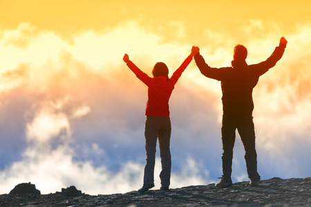 peak: Happy winners reaching life goal - success people at summit. Business achievement concept. Two person couple together arms up in the air of happiness with accomplishment in the clouds at sunset. Stock Photo