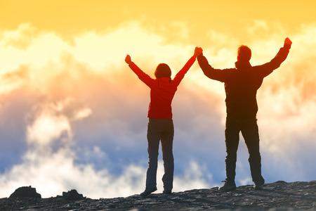 Szczęśliwi zwycięzcy osiągając cel życia - sukces ludzi na szczycie. Koncepcja osiągnięcia biznesowe. Dwie osoby para razem ręce w górę w powietrzu z radości z realizacji w chmury o zachodzie słońca.