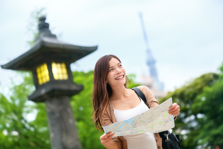 Travel in Tokyo - Asian tourist woman with map searching for directions with the Tokyo Skytree tower in the background. Young chinese adult visiting the city in Japan. Фото со стока