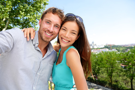 Couple tourists taking travel selfie self-portrait in Madrid park, Spain in summer. Young adults mixed race asian caucasian smiling at smartphone camera for a snapshot during their holidays in Europe. photo