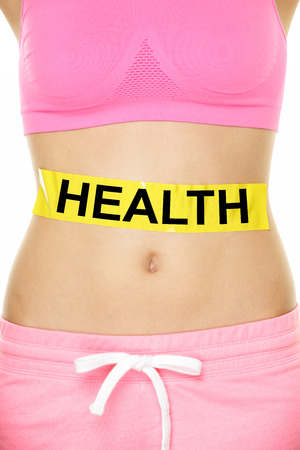 intestines: Health warning on stomach body - diet or nutrition concept. Word written on yellow label on lower body abdomen of female young adult to show caution about our health. Stock Photo