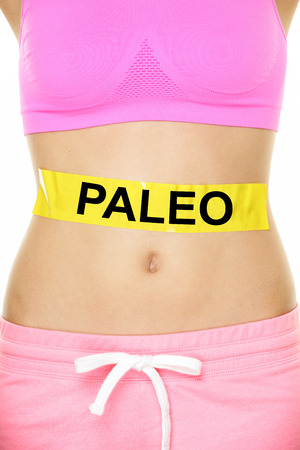 Paleo diet concept - closeup of womans stomach to show eating concept. New trend in nutrition based on hunter gatherer consumption of proteins. Yellow label as warning or caution applied on body.