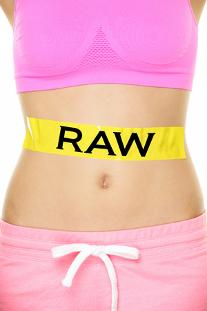 unprocessed: Raw food diet concept - closeup of womans stomach eating only raw ingredients. New trend in nutrition of only uncooked or unprocessed food. Yellow label as warning or caution applied on body. Stock Photo