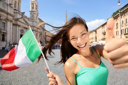bandera italiana: Mujer feliz turística bandera italiana en Roma, Italia. Asia chica joven que sostiene la bandera para el concepto de vacaciones de vacaciones o de intercambio de estudiantes para el aprendizaje de la lengua. Foto de archivo