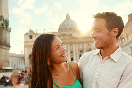Romantic couple lovers at sunset in Vatican, Italy. Italian vacation for honeymoon or weekend getaway of young asian caucasian adults in love in summer holidays. Stock Photo