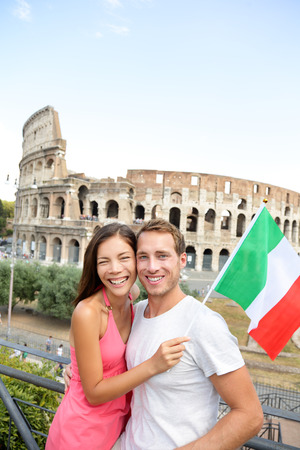 people travelling: Happy travel - couple tourists in front of Coliseum, Rome, Italy. Cheerful young Asian and Caucasian adults posing with Italian flag during their European holiday vacations in Europe.