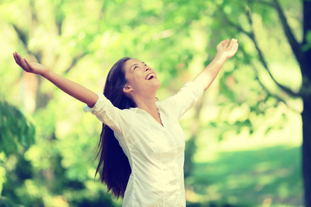 people and nature: Freedom happy woman feeling alive and free in nature breathing clean and fresh air. Carefree young adult dancing in forest or park showing happiness with arms raised up. Spring allergies concept. Stock Photo