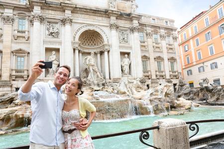 Toeristische paar op reis te nemen Selfie foto door Trevi-fontein in Rome, Italië. Gelukkig jong romantische paar reizen in Europa nemen zelfportret met smartphone camera. Man en vrouw samen gelukkig