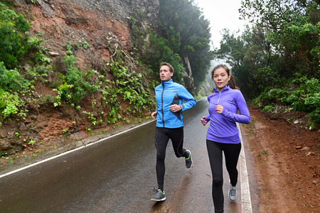 cardio fitness: Healthy lifestyle people running on country road exercising. Runners jogging on mountain road training for marathon. Asian woman and Caucasian man wearing waterproof sports clothing for wind and rain.