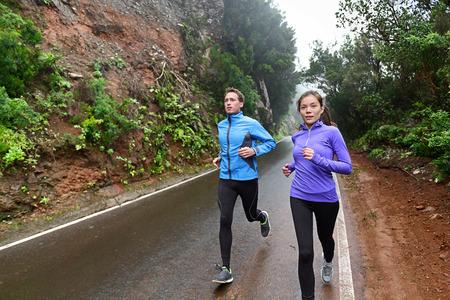 uomo sotto la pioggia: Stile di vita persone sane in esecuzione sulla strada di campagna che esercitano. Runners fare jogging sulla formazione strada di montagna per la maratona. Donna asiatica e caucasica uomo che indossa abbigliamento impermeabile sportivo per il vento e la pioggia. Archivio Fotografico