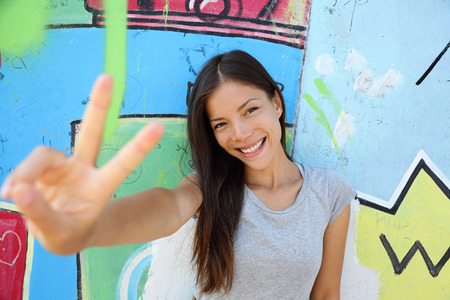 peace: Urban young girl showing v peace sign in city. Cool Asian woman leaning on graffiti background at the Berlin wall, Germany. Modern portrait.
