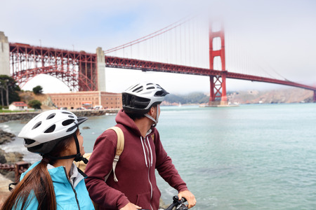 gate: Golden gate bridge - biking couple sightseeing in San Francisco, USA. Young couple tourists on bike guided tour enjoying famous travel landmark in California, USA.
