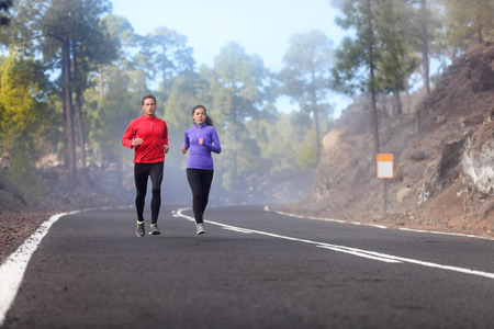 cardio fitness: People running - athlete runners training jogging in cloudy and cold weather. Exercising runner couple working out living healthy lifestyle training for marathon together on mountain road.