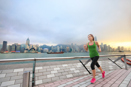 Sport woman runner running in Hong Kong skyline. Asian chinese fitness athlete jogging training living healthy lifestyle on Tsim Sha Tsui Promenade and Avenue of Stars in Victoria Harbour, Kowloon.
